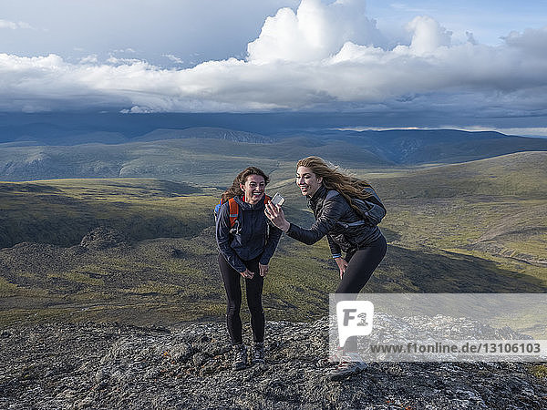 Two women using their cell phone to take a self-portrait and exploring the mountains and wilderness of the Yukon around Haines Junction; Yukon  Canada