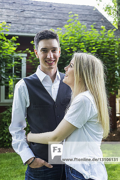 Portrait of a young couple standing in a backyard; Bothell  Washington  United States of America