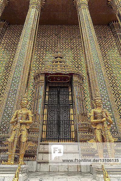Temple of the Emerald Buddha golden guardians  Grand Palace; Bangkok  Thailand
