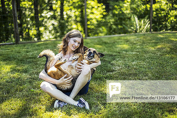 Teenage girl holding her dog on a grass field in a park; Surrey  British Columbia  Canada