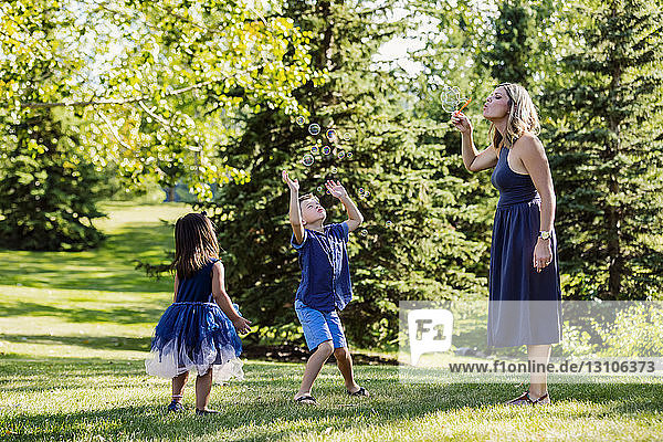 A mother blowing bubbles for her kids while on a family outing in a park on a warm fall day; Edmonton  Alberta  Canada