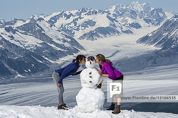 Women kissing the cheeks of a snowman on a mountaintop in Kluane National Park and Reserve; Haines Junction  Yukon  Canada