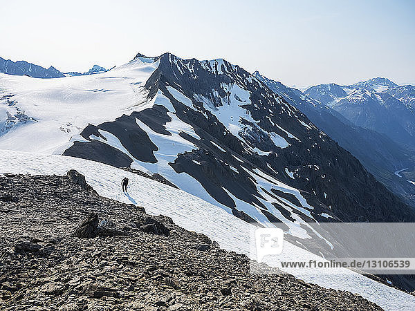 Person hiking across the snow on a mountain in Kluane National Park and Reserve; Haines Junction  Yukon  Canada