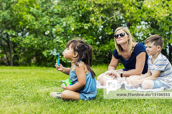 A young mother watching her daughter blowing bubbles while sitting on a blanket with her baby and her son in a city park on a warm sunny day; Edmonton  Alberta  Canada