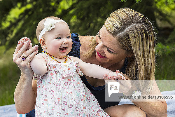 A young mother playing with her baby girl and holding her hands while they sit on a blanket in a park on a warm summer day; Edmonton,  Alberta,  Canada