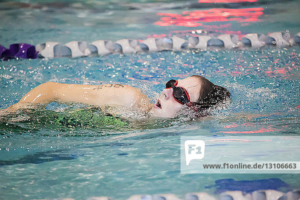 A young woman swimming laps in a lane during a triathalon race; Plano  Texas  United States of America