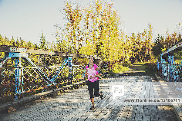 An attractive middle-aged woman running across a bridge while working out and listening to music on her smart phone during a beautiful warm fall evening in a city park; Edmonton  Alberta  Canada