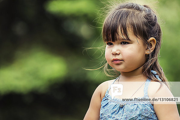 A portrait of a beautiful preschooler girl looking away while spending time in a city park on a warm sunny day; Edmonton,  Alberta,  Canada