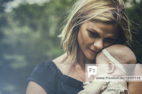 A young mother cuddling her sleeping baby outdoors in a park and deep in thought about her child; Edmonton,  Alberta,  Canada