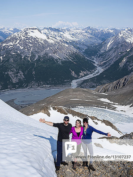 A group of friends enjoying a sunny afternoon on a mountaintop in Kluane National Park and Reserve; Haines Junction  Yukon  Canada