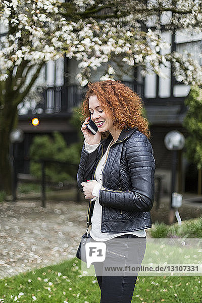 Woman talking on a cell phone while standing outside; North Vancouver  British Columbia  Canada