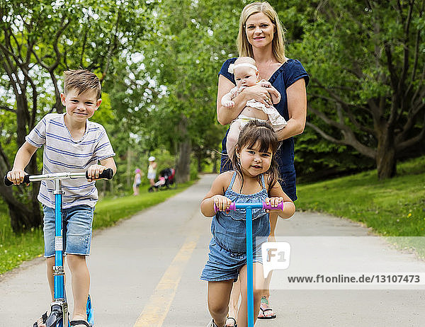 A young mother walking and holding her baby while watching her other kids riding their scooters on a trail in a park on a warm summer day; Edmonton  Alberta  Canada