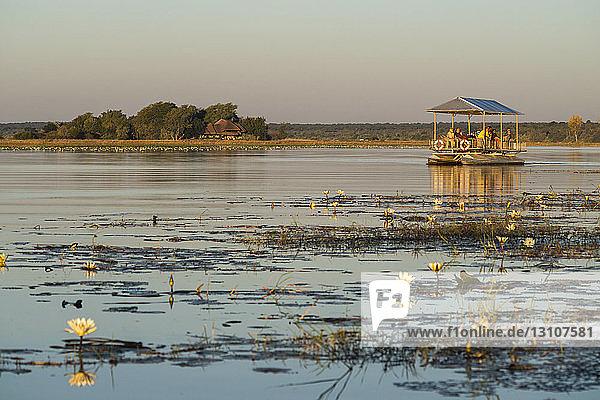 Cruising on the Chobe River at sunset looking for wildlife; Botswana