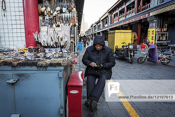 A vendor selling calligraphy sets at the Panjiayuan Antique Market; Beijing  China