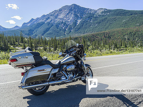 A motorcycle parked on the side of the road with view of the Rocky Mountains  Jasper National Park; Alberta  Canada