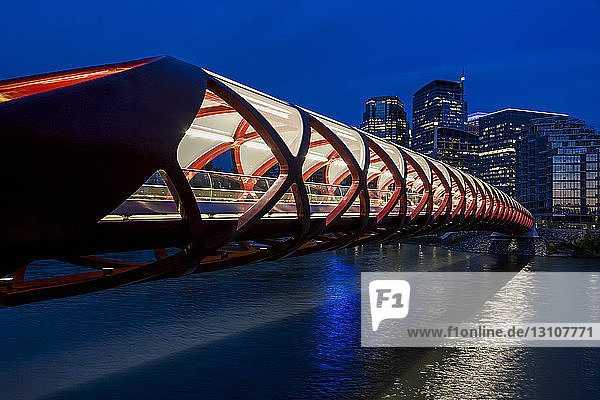 A red tunnel bridge across a river reflecting light at night with buildings in the background; Calgary  Alberta  Canada