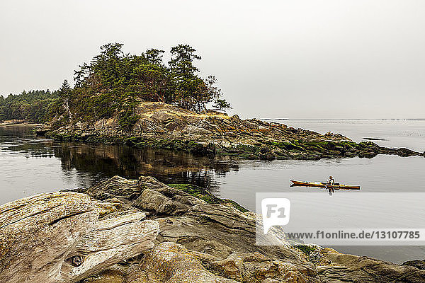A kayaker approaches Boat Passage on Saturna Island  Gulf Islands National Park Reserve; Saturna Island  British Columbia  Canada
