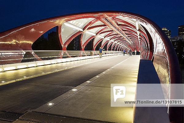 Glowing lights inside a pedestrian red metal bridge at night; Calgary  Alberta  Canada