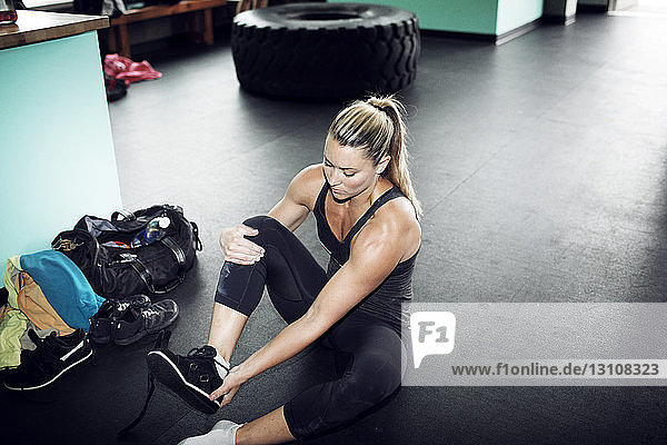 High angle view of female athlete removing shoes in gym