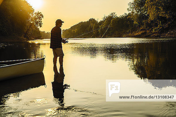 Side view of mid adult man fishing while standing in lake during sunset