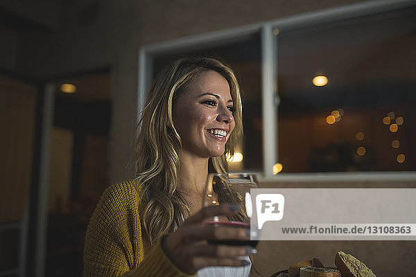 Smiling woman with wineglass looking away while standing at patio