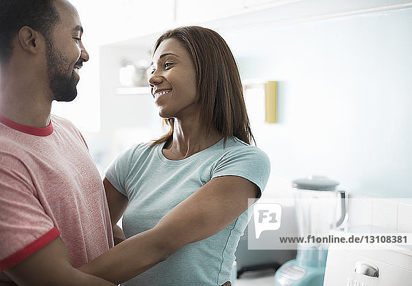 Couple embracing while standing in kitchen at home