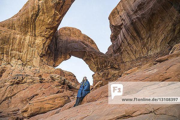 Niedrigwinkelansicht einer Frau  die auf einer Felsformation im Arches-Nationalpark sitzt
