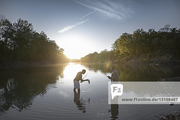 Side view of male friends fishing while standing in lake against sky during sunset