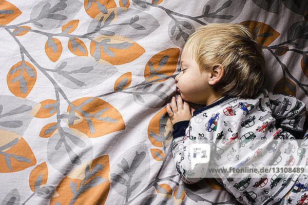 Hochwinkelansicht eines auf dem Bett schlafenden Jungen