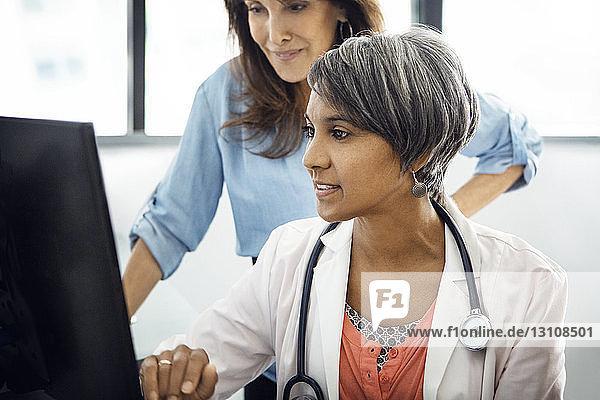 Ärztin am Computer mit Patienten in der Klinik Ärztin am Computer mit Patienten in der Klinik