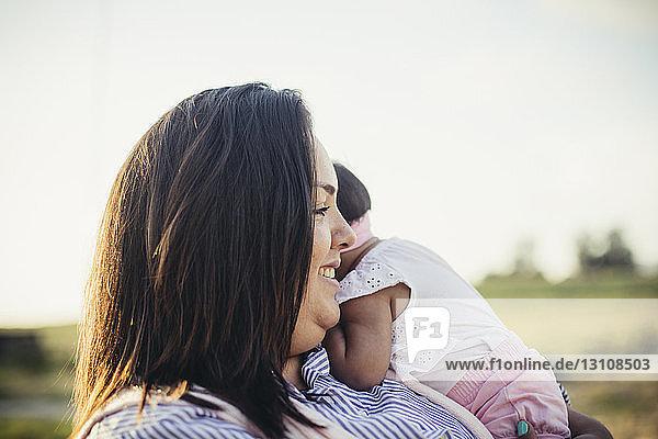 Mutter trägt Tochter  während sie bei Sonnenuntergang am klaren Himmel auf der Ranch steht