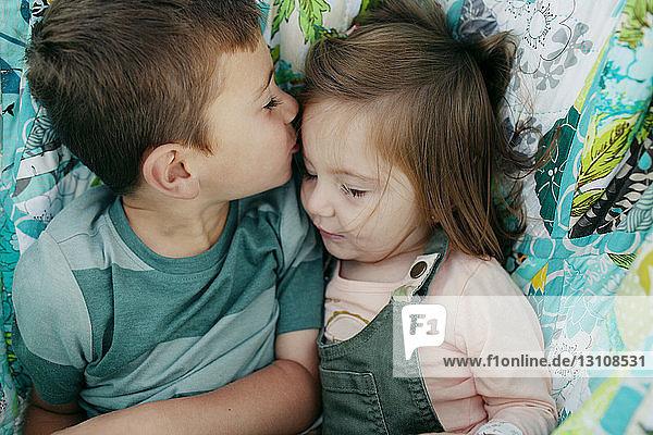 Boy kissing sister while lying in hammock