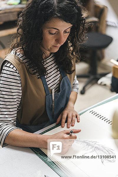 Hochwinkelansicht einer Kunsthandwerkerin  die in der Werkstatt sitzend auf einem Buch zeichnet