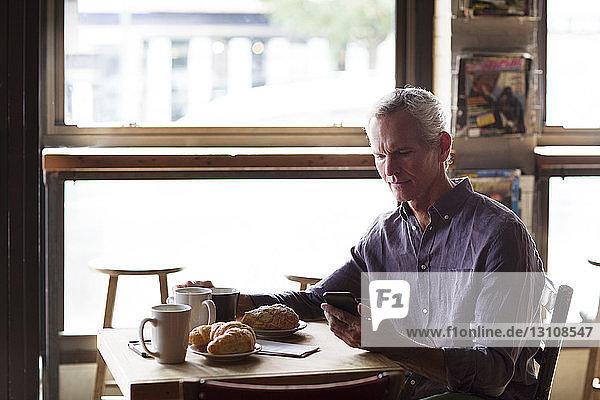 Erwachsener Mann telefoniert bei Croissants und Kaffee am Tisch im Café