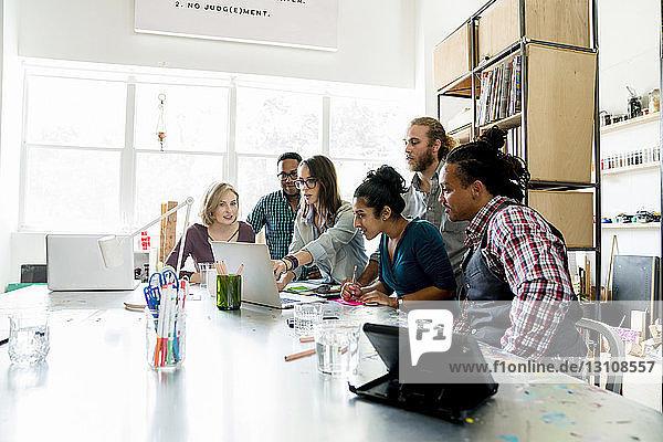 Geschäftsfrau erklärt am Laptop den Kollegen am Konferenztisch