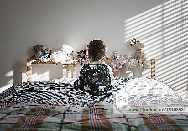 Rückansicht eines Jungen  der zu Hause auf dem Bett sitzt