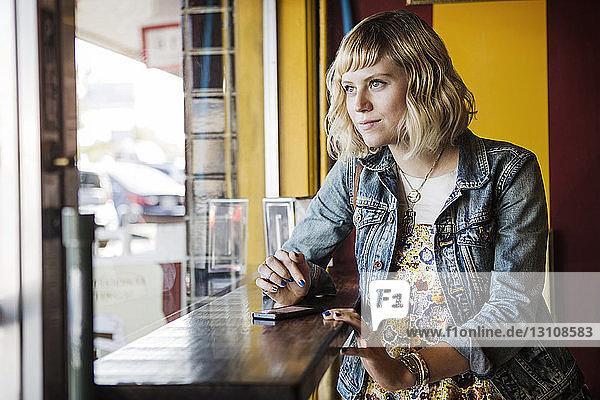 Nachdenkliche Frau schaut durch das Fenster im Café weg