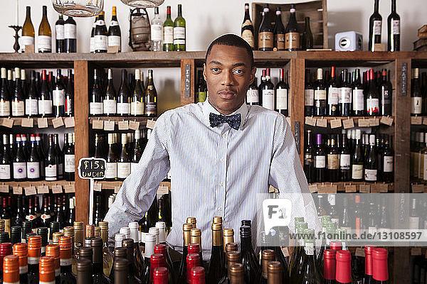 Porträt eines selbstbewussten männlichen Kleinunternehmers im Weinladen stehend