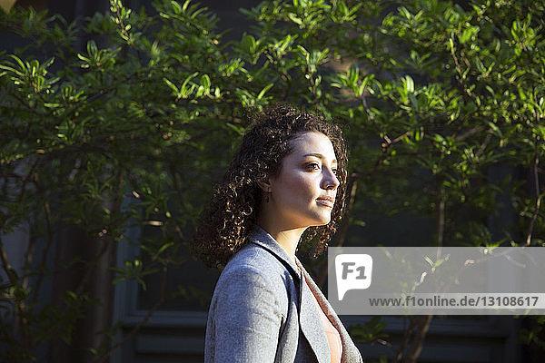 Seitenansicht einer nachdenklichen Geschäftsfrau nach Pflanzen