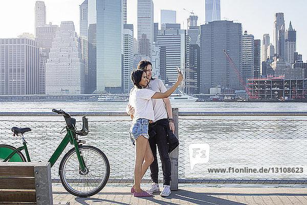 Pärchen  das sich am Handy selbstständig macht  während es an Fahrrädern gegen das Stadtbild steht