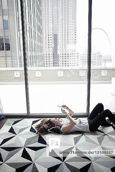 Frau  die ein Smartphone mit hohem Blickwinkel benutzt  während sie zu Hause am Fenster auf dem Teppich liegt
