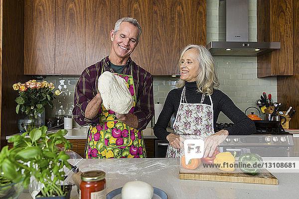 Frau schneidet Paprika  während der Mann zu Hause in der Küche Pizzateig herstellt