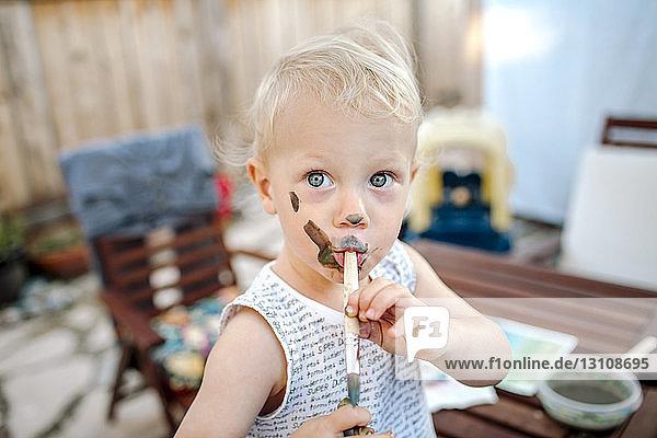 Porträt eines kleinen Jungen mit unordentlichem Gesicht  der den Pinsel in den Mund nimmt  während er auf dem Hof steht