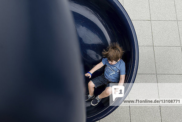 High angle view of boy playing on slide in playground