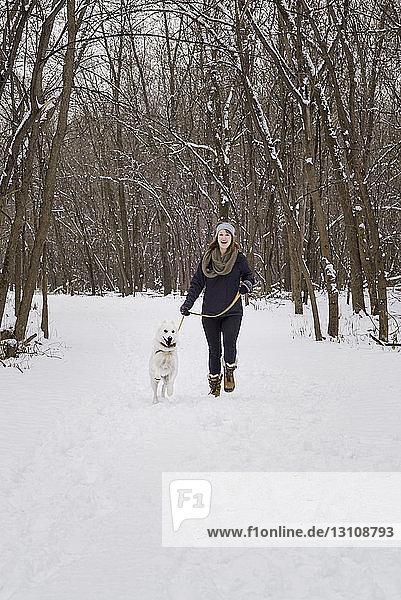 Glückliche Frau geht mit Hund auf schneebedecktem Feld gegen kahle Bäume