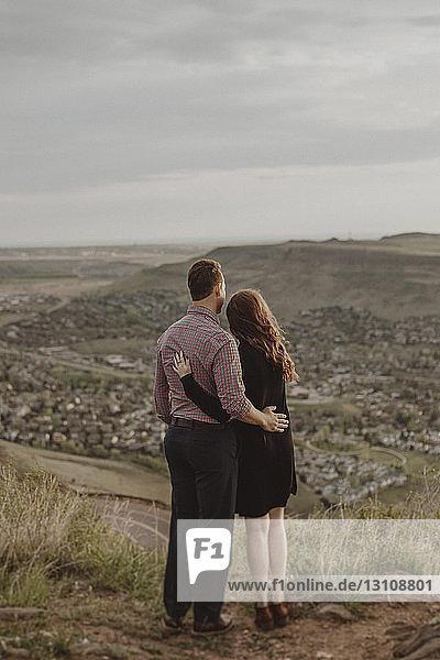 Ein junges Paar in voller Länge schaut auf den Blick  während es auf dem Feld gegen den Himmel steht