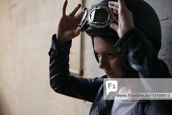 Woman adjusting flying goggles at workshop