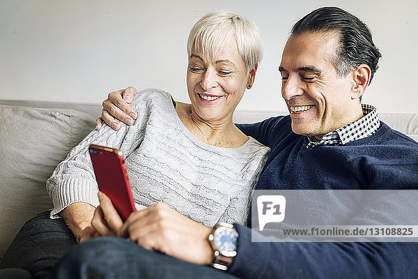 Senior couple looking at smart phone while sitting on sofa at home