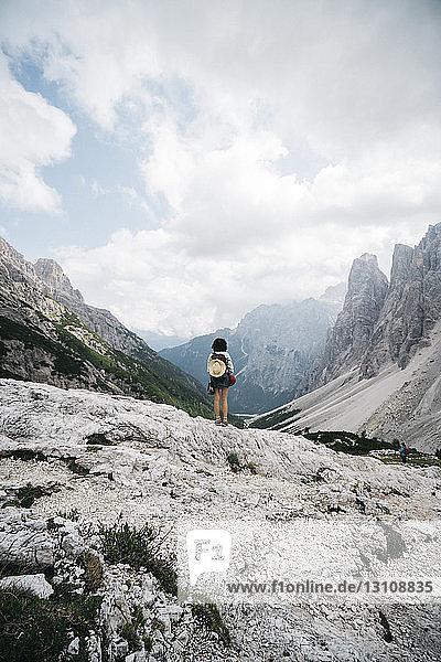 Rückansicht einer Wanderin mit Rucksack  die auf einem Berg vor bewölktem Himmel steht