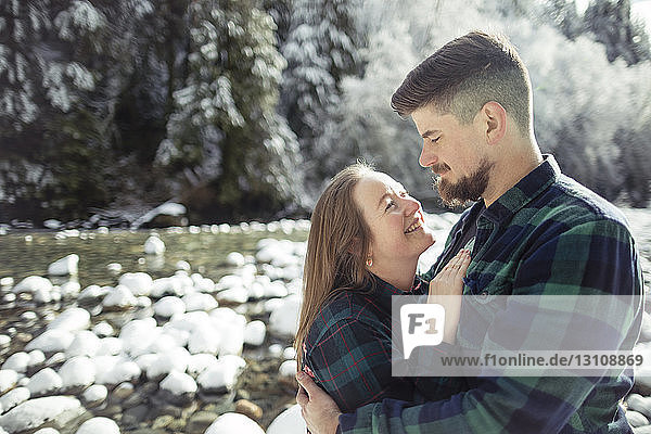 Smiling woman looking man while standing in forest at Lynn Canyon Park during winter